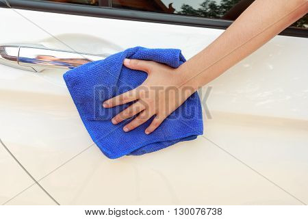 Concept of woman hand cleaning car using microfiber cloth