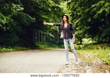 Young woman hitchhiking on the road surrounded by trees