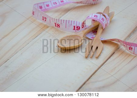 Wooden kitchen wooden spoon and fork on wooden background with measuring tape of the tailor diet concept.