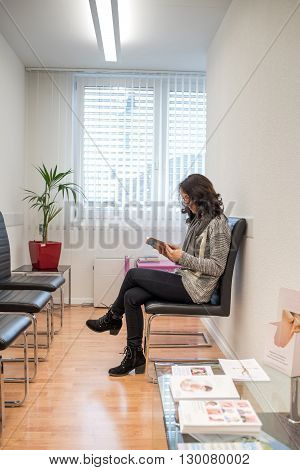 Young patient reading a magazine in the doctor's waiting room