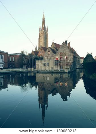 View of cathedral in the center of Bruges, Belgium, and it's reflection in water