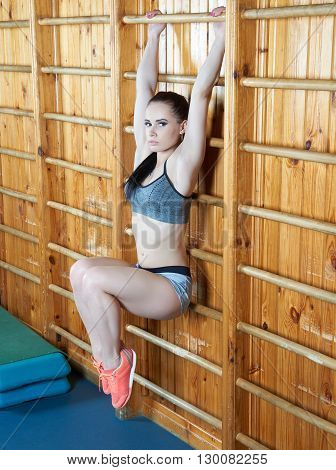 Beautiful young woman training her abdomen and leg muscles on the wall bars in the gym