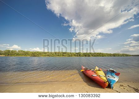 Camping with kayaks on the beach on a sunny day.