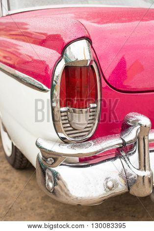 Classic car with close up on the rear headlights in rainy weather.