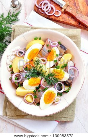 Salad of herring, boiled potatoes, eggs and onions with olive oil.