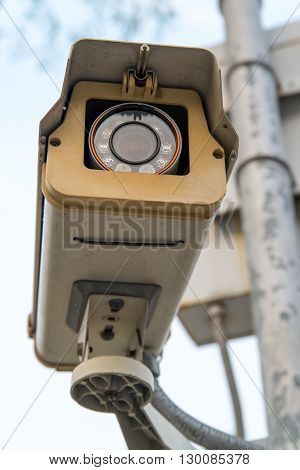 Close-up of a CCTV surveillance camera spying on people.