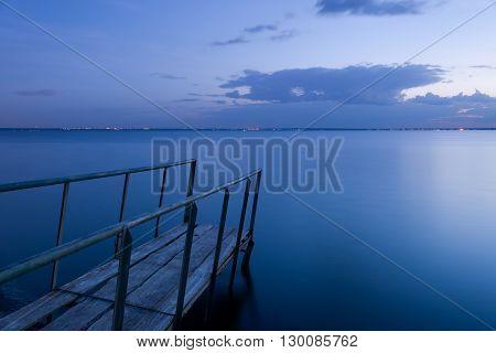 Old wooden fishing bridge to the sea.