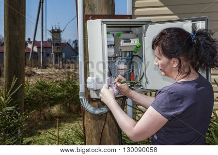 Peasant Woman takes readings of the electric meter and invoice near farm house in countryside.