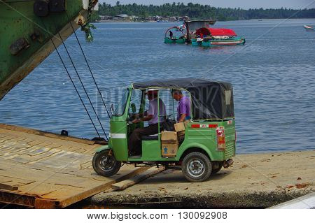 Muisne, Ecuador - March 16, 2016: Green traditional tuktuk transportation vehicle entering ferry from Muisne pier .