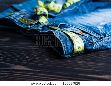 jeans and centimeter on a wooden background close up
