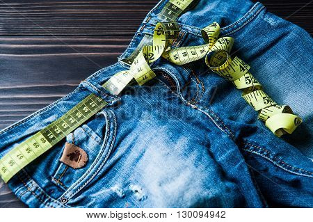 jeans and centimeter on a wooden background. clothing