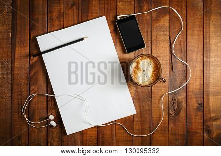 Blank mock-up for design presentations and portfolios. Paper letterhead coffee cup smartphone pencil and headphones on wooden table background. Blank ID set. Top view.