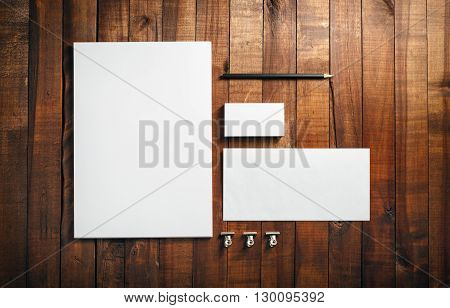 Photo of blank stationery set on wood background. Blank stationery and corporate identity template. Blank letterhead business cards envelope and pencil. Top view.