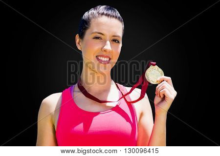 Portrait of sportswoman is smiling and showing her medal