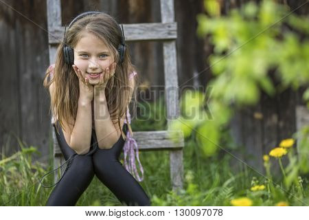 Cute girlie enjoys music with headphones on sitting in the courtyard of a village house.