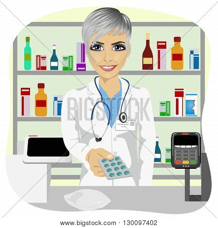 female pharmacist giving pills in a blister pack standing in a drugstore in front of medications on showcase