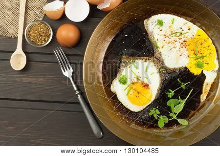 Fried fried egg on steel pan. Preparing homemade dietary supplements. Pan on a dark wooden table. Fried eggs.