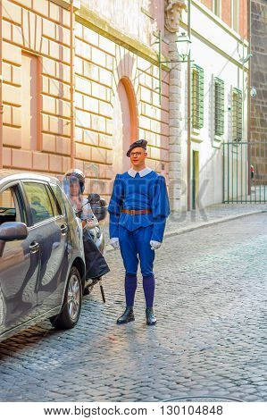 VATICAN, ITALY - JUNE 13, 2015: Swiss guard with nice blue uniform outside in Vatican streets, nice uniform with red belt and black beret.
