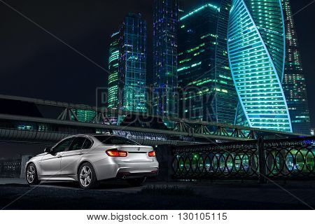 Moscow, Russia - May 07, 2015: Modern car BMW F30 stay near Moscow City district at night
