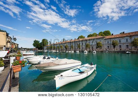 Peschiera del Garda Italy - May 03 2016: The boats moored in the canal of old city sunny spring day