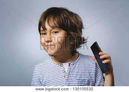 Portrait of happy boy with mobile going surprise on gray background.