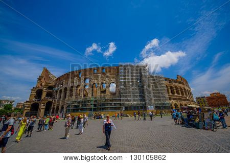 ROME, ITALY - JUNE 13, 2015: Nice view of Roman Coliseum from outside, people walking around and reconstruction works.