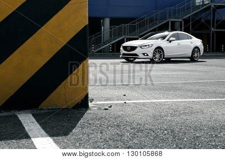 Krasnodar, Russia - September 07, 2014: White car Mazda 6 stay on parking near city building at daytime