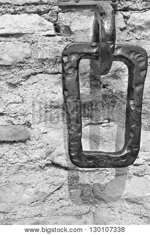 the old iron hinge or arm is intended for mooring of boats and placed on a stone wall closeup of monochrome tone