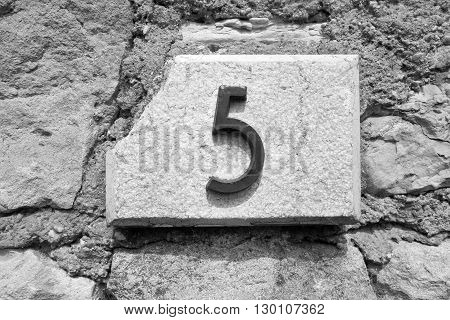 the figure five is placed by a closeup on a stone wall for the indication of house number