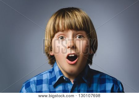 Portrait of happy boy going surprise on gray background.