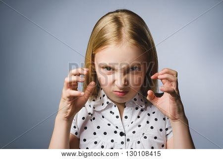 Portrait of angry girl with hands up yelling isolated on gray background. Negative human emotion, facial expression. Closeup.