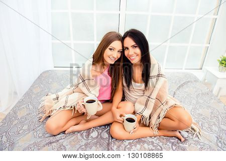Two Sisters Siting On Bed And Basking With Plaid And Tea