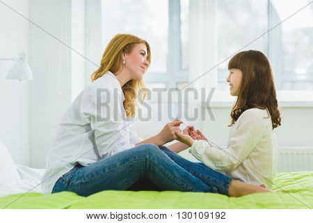 daughter and mother tenderly hold each other's hands.