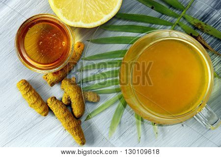 Healthy Haldi or Turmeric with honey and lemon antioxidant tea on a grey background.