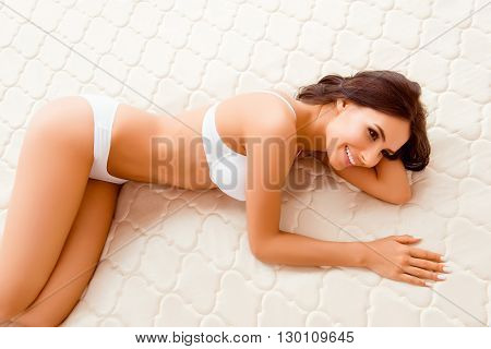 Portrait Of Attractive Smiling Woman Lying On Bed N Lingerie