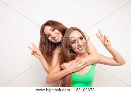 Two Pretty Smiling Girls  Gesturing With Two Fingers
