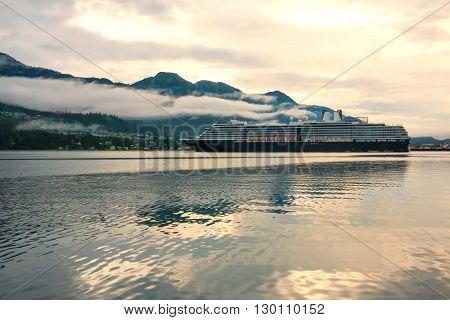 Cruise ship at port in Juneau, Alaska, under cloudy skies at a golden hour sunset