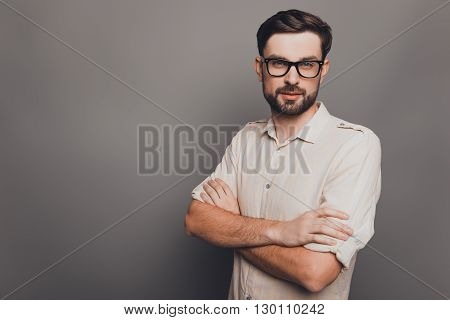 Successful Young  Businessman In Glasses With Crossed Hands On Gray Background