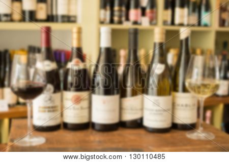 Deliberately blurred image of a row of bottles of wine between two wineglasses on wooden surface and wine collection in the background.