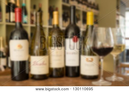 Blurred photo of a row of five wine bottles and a pair of wine glasses with a wine collection in the background