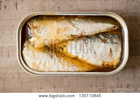 Overhead of an opened can of sardines or herring in oil on wooden surface