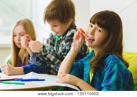 happy Little girls and boy drawing pictures. Indoor at room. Girl dreaming in front of children.