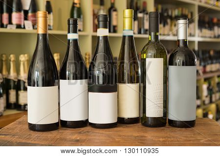 A row of sealed and unlabeled bottles of wine with a wine collection in the background