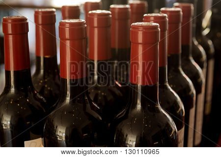 Three rows of bottles of wine each sealed in red