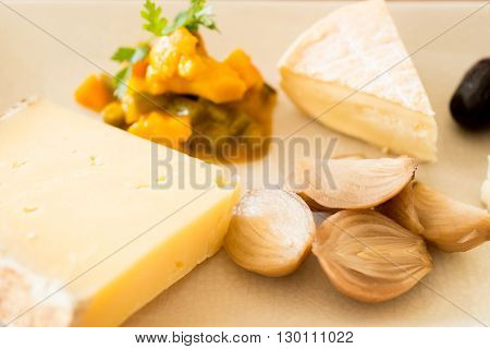Slices of gourmet cheese beside vegetable mush side dish and cooked shallots.