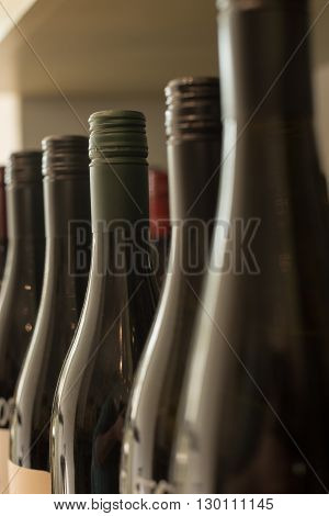 A row of unlabeled and sealed dark wine bottles.