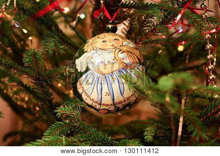 Christmas ball with the image of the girl-angel on the Christmas tree among the garlands and streamers