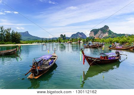 Hat Noppharat Thara Thailand - January 5 2013: Long-tail boats for tourist trips moored in bay with limestone karsts on horizon at Hat Noppharat Thara in Krabi Province southern Thailand