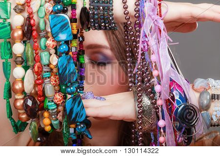 Pretty young woman wearing bracelets holding many plentiful of precious jewelry necklaces beads. Portrait of gorgeous fashion girl in studio on gray.