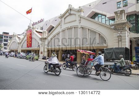 Hanoi, Vietnam - May 14, 2016: Cyclo and motorcycle traveling in front of Dong Xuan market in Hanoi capital. Dong Xuan market, established on 1889 by French, is the oldest and largest market in Hanoi.